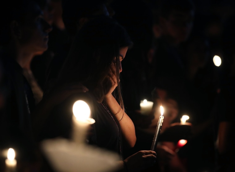 Students and family members grieve at a candlelight vigil.