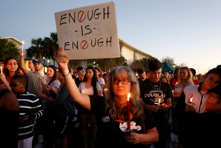 Mourners stand during a candlelight vigil.