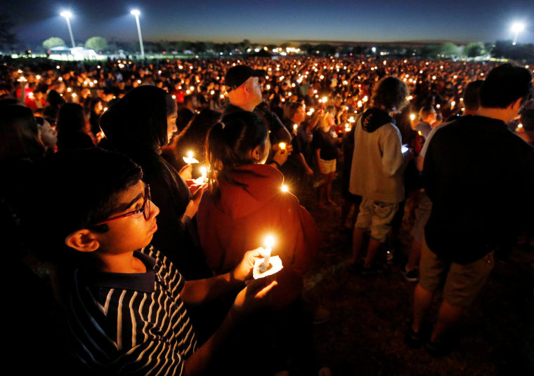 People attend a candlelight vigil.