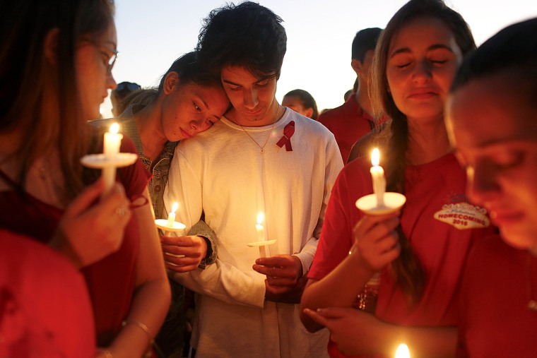 Students mourn at a candlelight vigil.