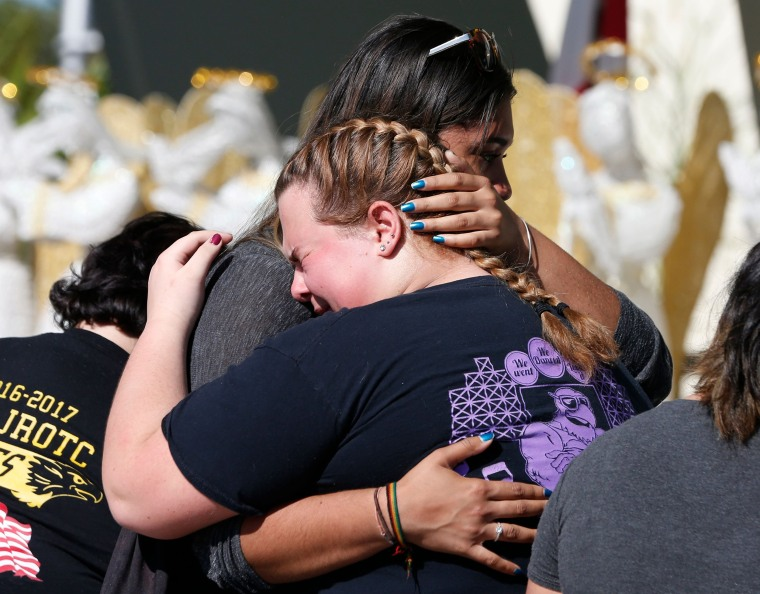 Mourners embrace after placing flowers on a makeshift memorial.