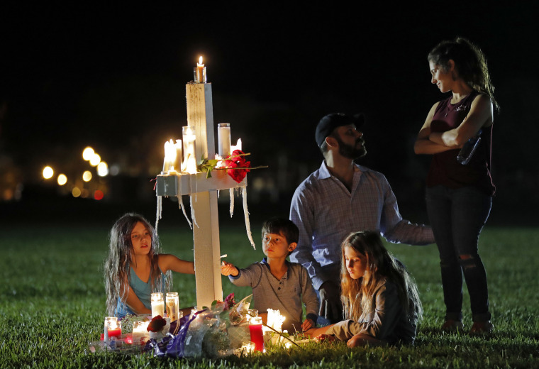 Rich and Rachel Castleberry visit one of seventeen crosses after a candlelight vigil with their children Mila, 9, left, Jack, 5, center, and Lucy, 7.