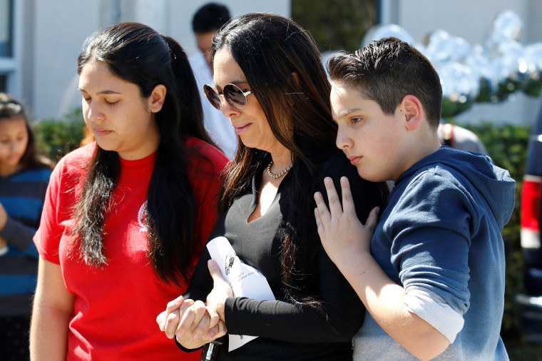 Students and parents from Marjory Stoneman Douglas High School attend a memorial.