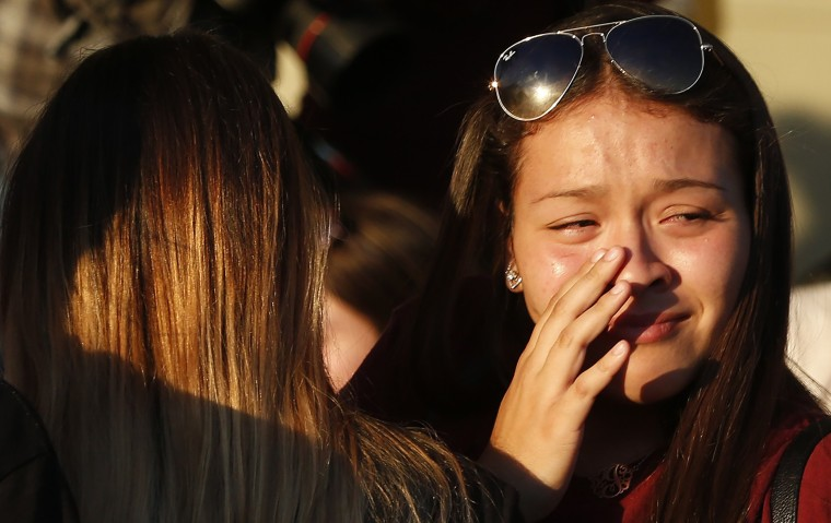 Students grieve after they placed flowers on a makeshift memorial.