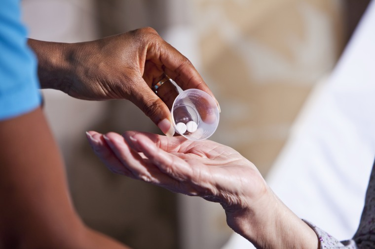 Image: Hand of nurse giving patient medication