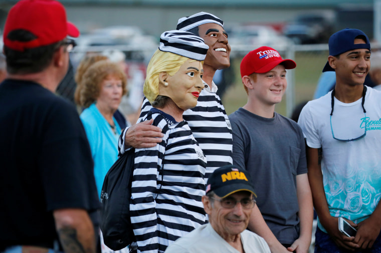 Image: People dressed as Clinton and Obama in prison jumpsuits circulate in the crowd as Trump rallies with supporters in Tallahassee, Florida