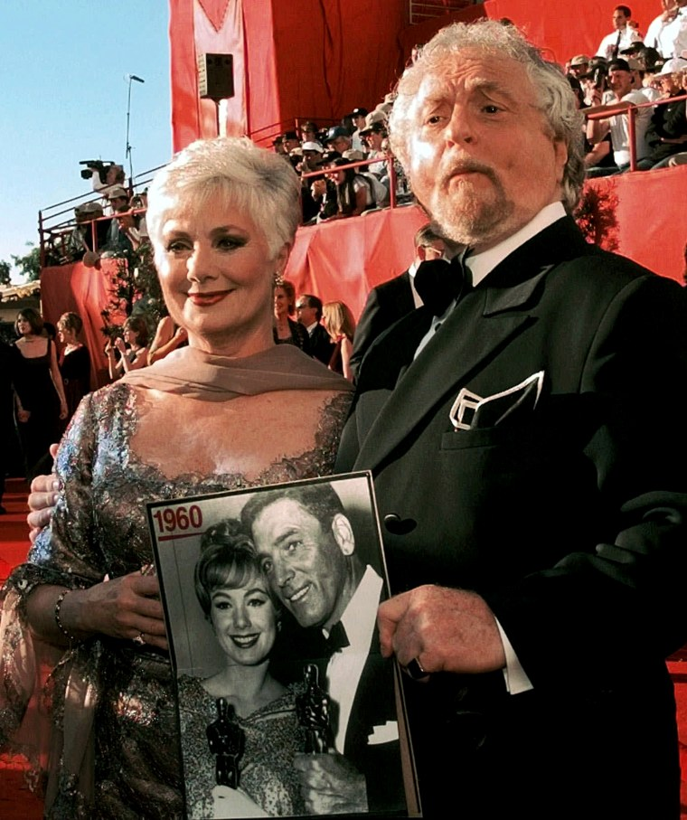 """Marty Ingles shows off a picture of his wife, Shirley Jones, as they arrive at the 70th Academy Awards at the Shrine Auditorium in Los Angeles Monday, March 23, 1998. The picture, from 1960, shows Jones and Burt Lancaster after they won Oscars for their roles in """"Elmer Gantry."""""""