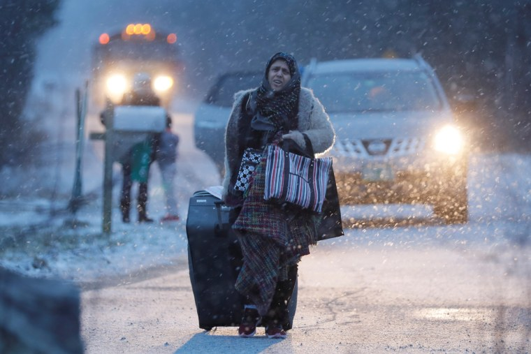 Image: A woman walks towards the border to cross at the U.S.-Canada border after arriving in a taxi with a group that claimed to be from Syria into Hemmingford