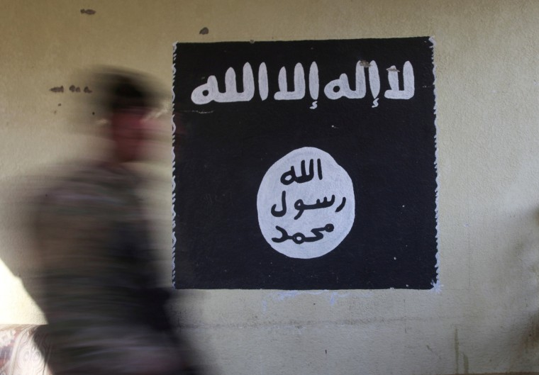 Image: FILE PHOTO: A member of the Iraqi rapid response forces walks past a wall painted with the black flag commonly used by Islamic State militants, during battle in the Wahda district of eastern Mosul, Iraq
