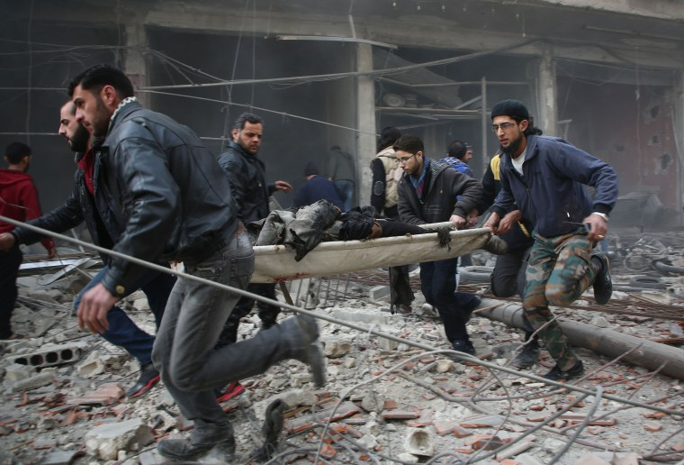 Image: Syrian rescuers evacuate a person injured following airstrikes