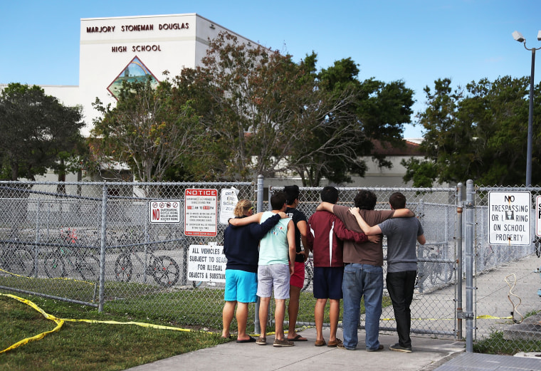 Image: People look on at the Marjory Stoneman Douglas High School