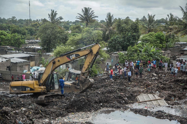 Image: Residents stand next to an excavator working at the site of a dump collapse