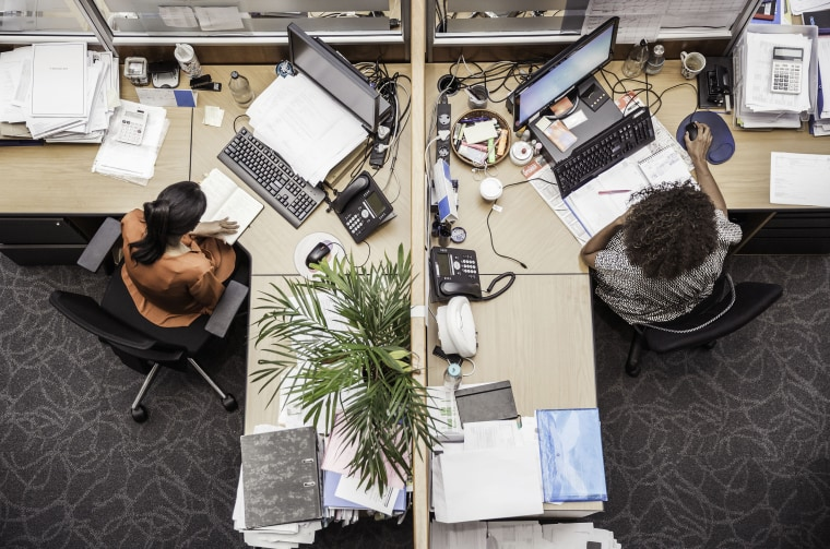 Image: Overhead view of two businesswomen at office desk
