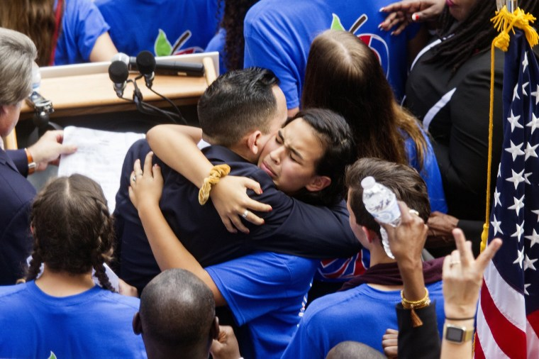 Image: Victoria Mejai, a sophomore from South Broward High School hugs Florida Rep. Carlos Guillermo Smith