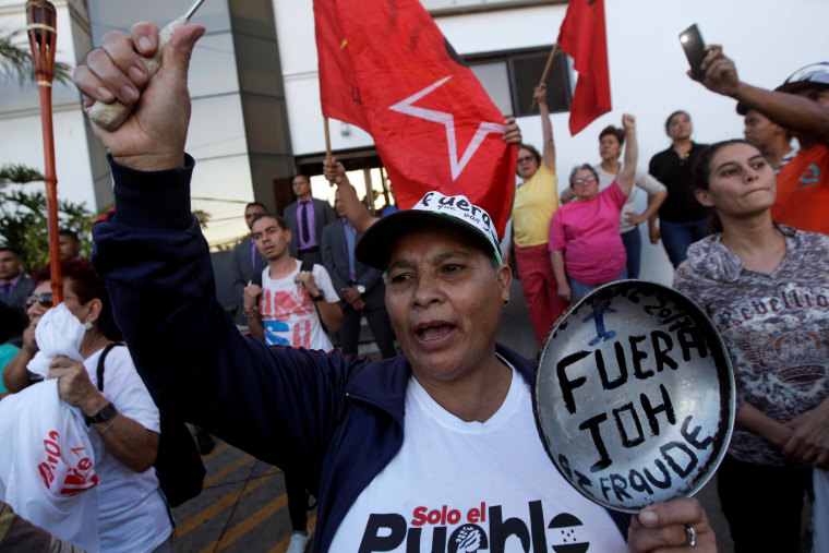 """Image: Demonstrator holds a frying pan reading \""""JOH out, Fraud\"""", referring to Honduran President Juan Orlando Hernandez, during a protest against Hernandez in Tegucigalpa"""