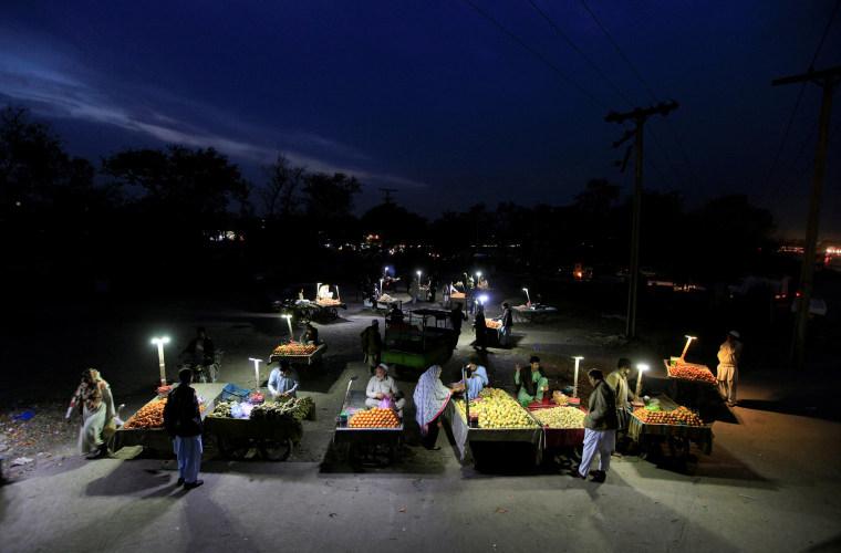 Image: Customers shop at an open air evening fruit market along a road in Rawalpindi