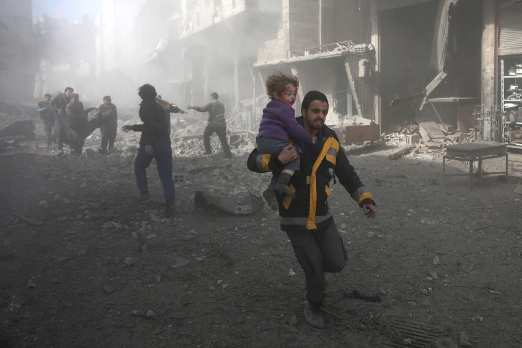 A Syrian man carries a child injured in government bombing in the rebel-held town of Hamouria, in the besieged Eastern Ghouta region on the outskirts of the capital Damascus, on Feb. 19, 2018.