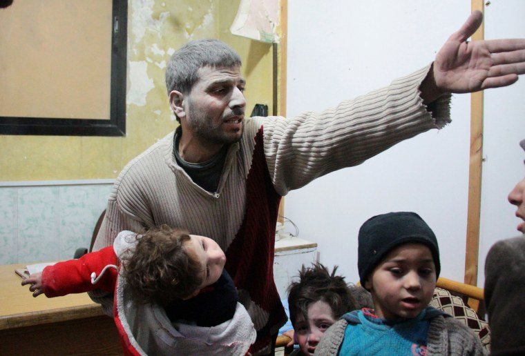 A Syrian man holds a child who was wounded in air strikes on the Syrian village of Mesraba in the besieged Eastern Ghouta region, at a make-shift hospital in Douma on Feb. 19.