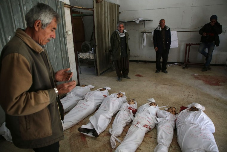 A Syrian man prays next to bodies prepared for burial in the rebel-held town of Arbin on Feb. 20.