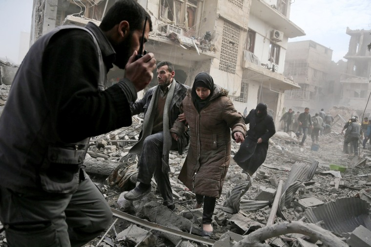 A member of the Syrian civil defense speaks on a wireless transmitter as other civilians flee from an area hit by a regime air strike in the rebel-held town of Saqba on Feb. 20.