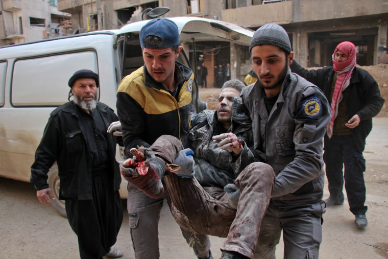 Civil defense volunteers, known as the White Helmets, carry a wounded man into a makeshift hospital in Douma on Feb. 20.