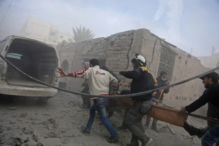 Members of the Syrian Civil Defense evacuate an injured civilian on a stretcher in the town of Saqba, on Feb. 20.