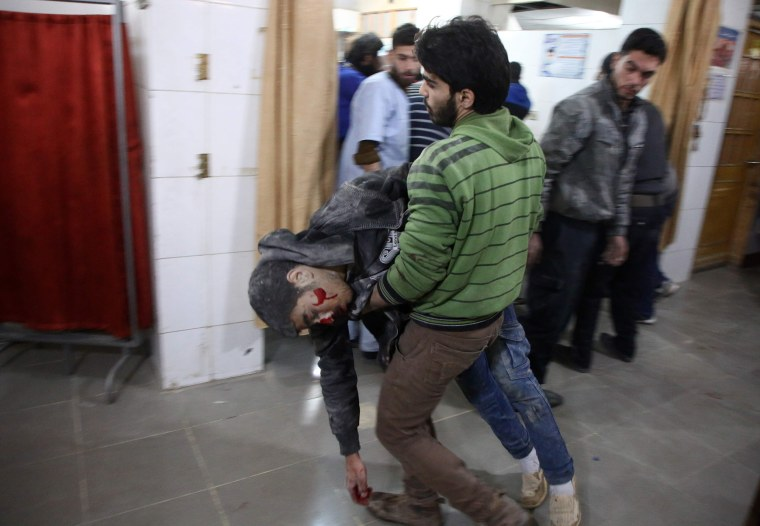 A man carries a severely wounded Syrian in Kafr Batna on Feb. 21.