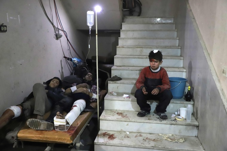 Wounded Syrians wait to receive treatment at a make-shift hospital in Kafr Batna on Feb. 21.