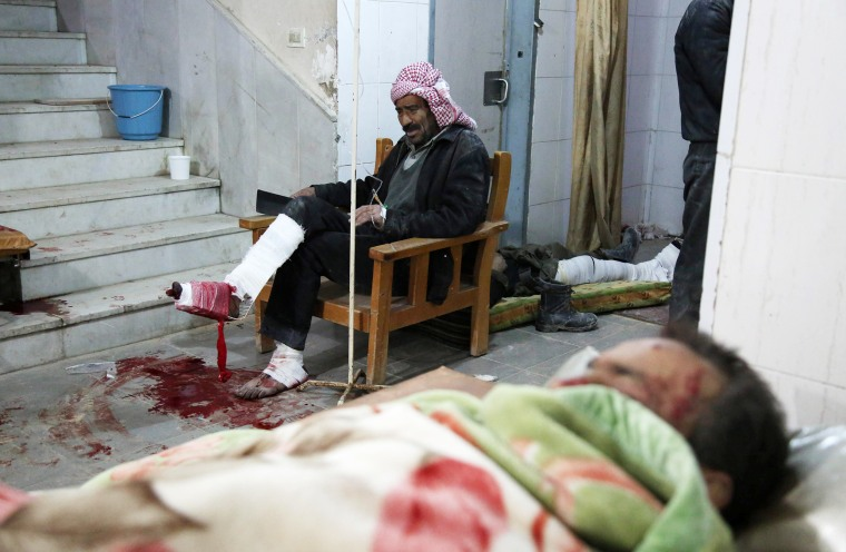 Wounded Syrians sit in wait in Kafr Batna on Feb. 21.