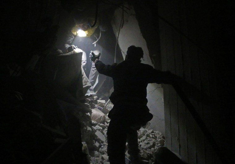 Syrian rescuers work at the site of Syrian government bombardments in Douma on Feb. 22.