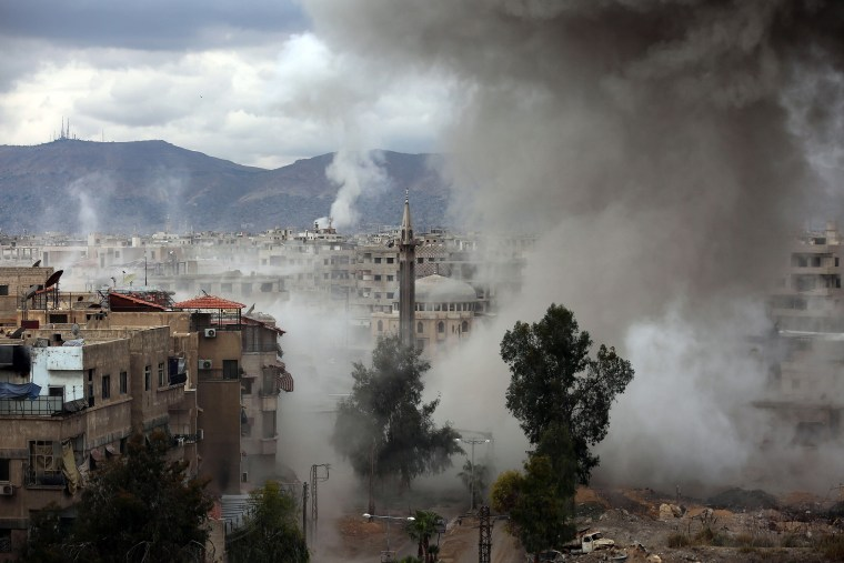 Smoke billows following Syrian government bombardments on Kafr Batna on Feb. 22.