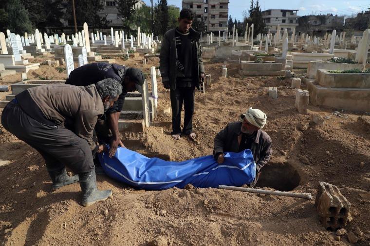 Syrians prepare to bury a body in Kafr Batna on Feb. 22.