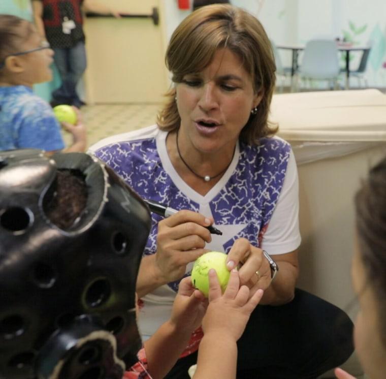 Image: Gigi Fernandez signs tennis balls for kids at Del Nino Children's Hospital