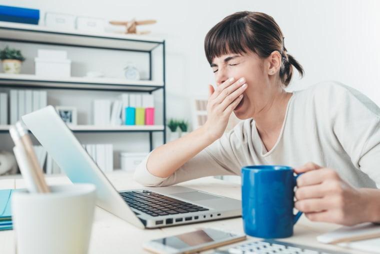 Image: Woman yawning at work