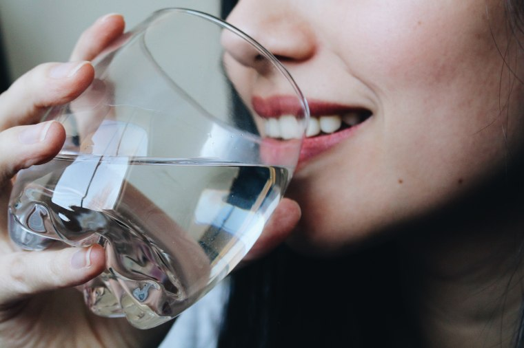 Image: Close-Up Midsection Of Young Woman Drinking Water At Home