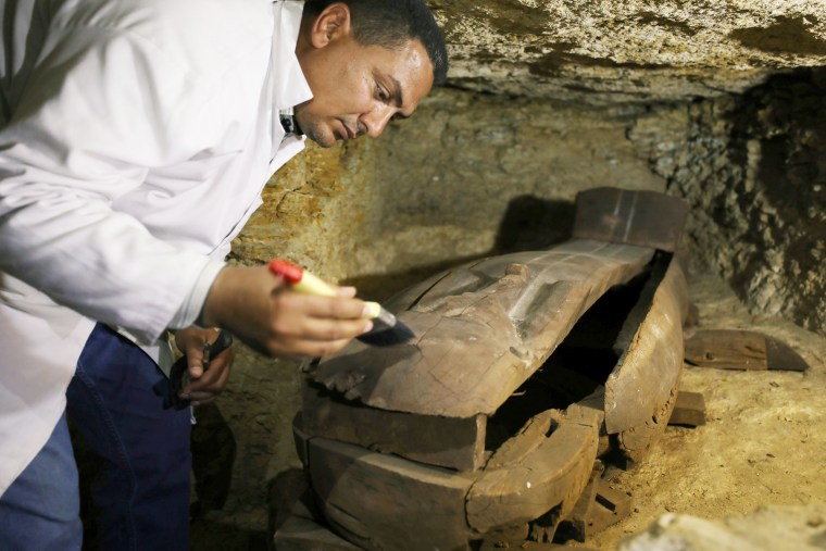 Image: An Egyptian antiquities worker brushes a coffin inside the recently discovered burial site in Minya, Egypt on Feb. 24, 2018.