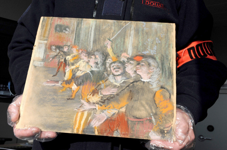 Image: A French custom officer holds a Degas painting stolen from a museum in Marseille nine years ago has been found on a bus near Paris, on Feb. 22, 2018.