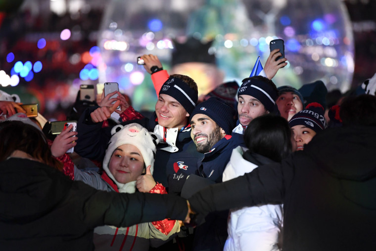 France's biathlon champion Martin Fourcade poses for a selfie with fellow athletes and volunteers.