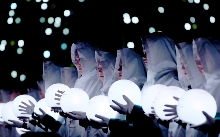 Artists hold light globes in the closing ceremony performance.