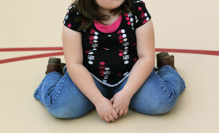 Image: A child sits on the gym floor during the Shapedown program for overweight adolescents and childre