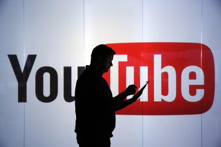 Image: A man stands in front of YouTube's logo at an office in London