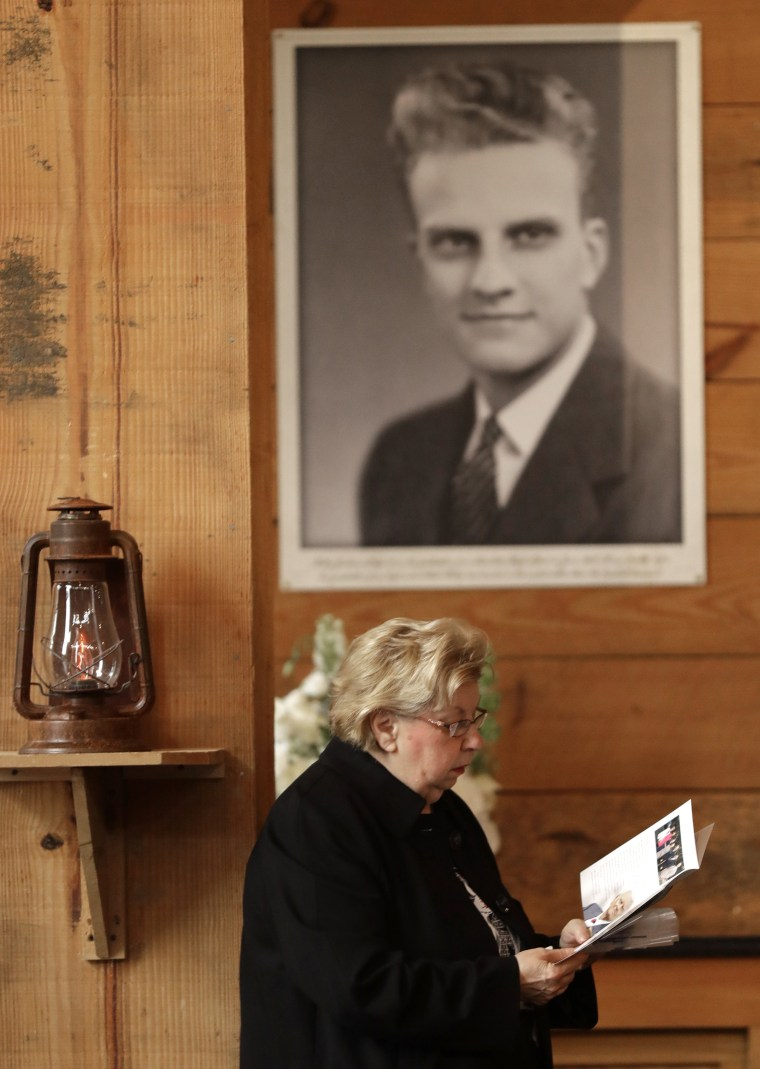 Image: A woman reads a brochure under a large photo of Billy Graham