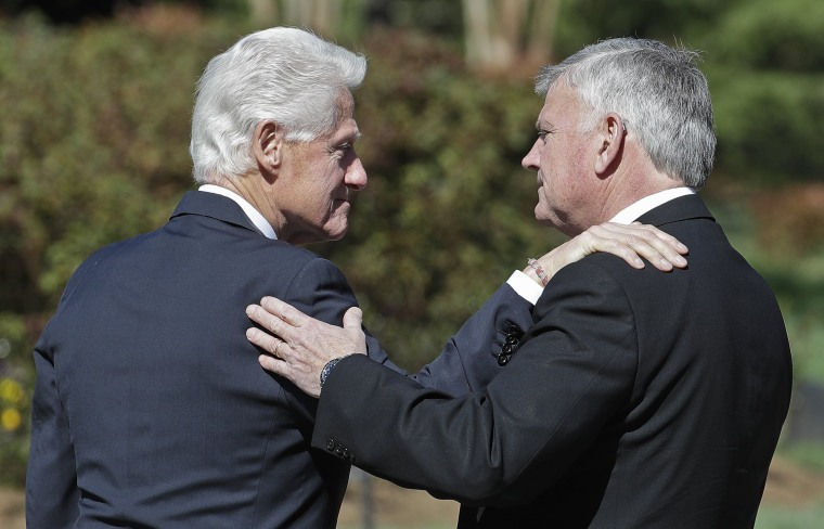 Image: Former President Bill Clinton, left, greets Franklin Graham