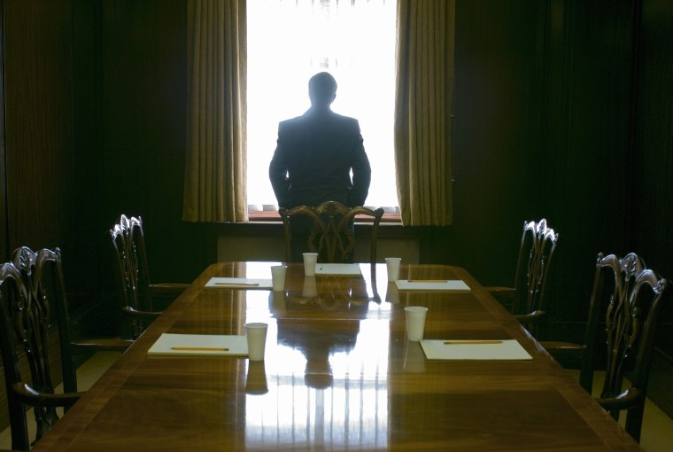 Image: A businessman looks out the window of a meeting room