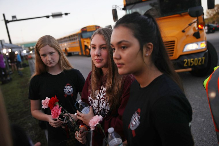 Image: Students wait at a crosswalk as they arrive to attend classes at Marjory Stoneman Douglas High School
