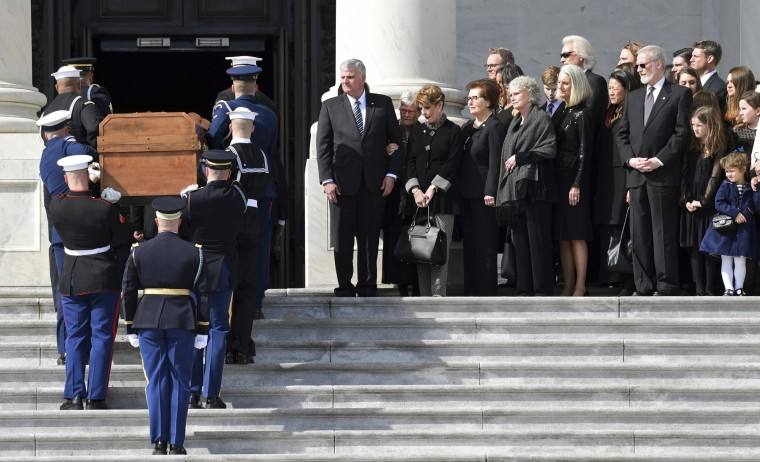 Image: The family of Rev. Billy Graham watches as his casket is carried up the steps of the U.S. Capitol
