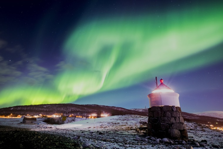 Image: Aurora borealis or northern lights are visible in the sky above a lighthouse to the village of Strand