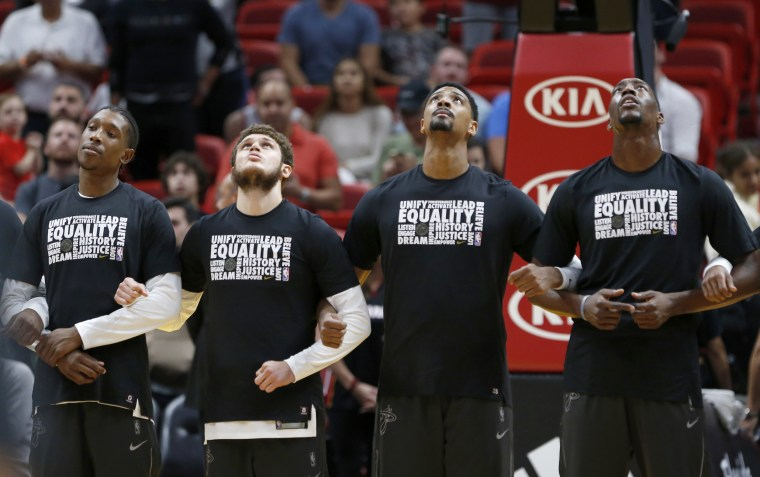 Image: In this Feb. 5, 2018, file photo, Miami Heat players stand together during the singing of the national anthem before the start of an NBA basketball game against the Orlando Magic in Miami.