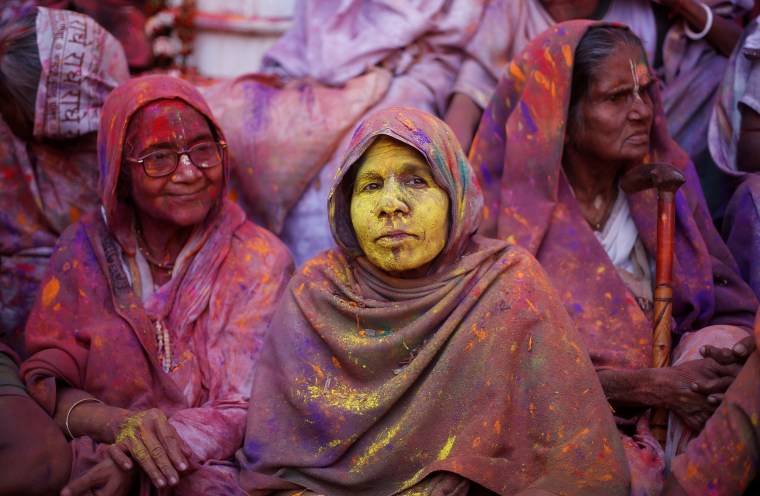 Image: Widows daubed in colours take part in Holi celebrations in the town of Vrindavan