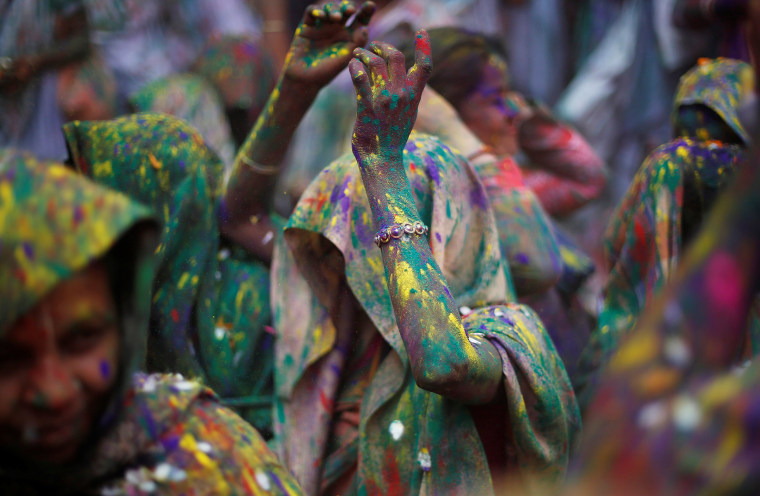 Image: Widows daubed in colours dance as they take part in Holi celebrations in the town of Vrindavan